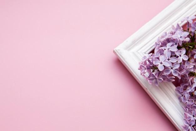 Flores lilás com uma moldura de madeira em um fundo rosa. conceito de primavera com o meu espaço.