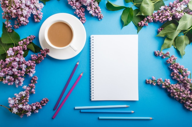 Flores lilás roxas e uma xícara de café com caderno e lápis de cor
