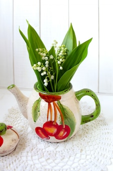 Flores lírios do vale em um bule de chá