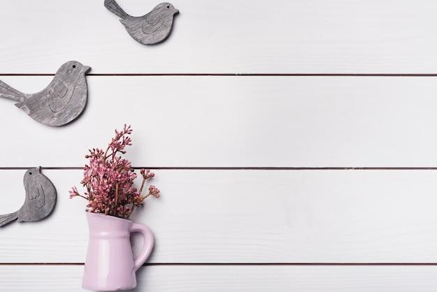 Flores minúsculas rosa em vaso de cerâmico com pássaros de madeira na mesa branca