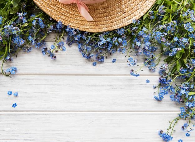 Flores miosótis e chapéu de palha