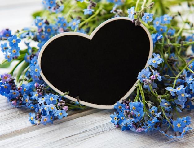 Flores miosótis e quadro em forma de coração preto sobre fundo branco de madeira