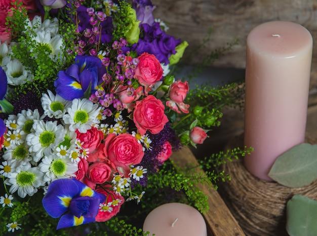 Flores mistas e velas de aroma-de-rosa.