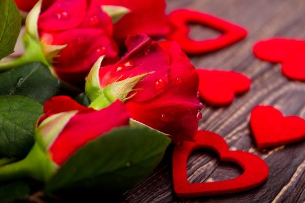 Flores molhadas em fundo de madeira. rosas com corações de tecido. pequeno presente grande alegria. demonstração de apreço.