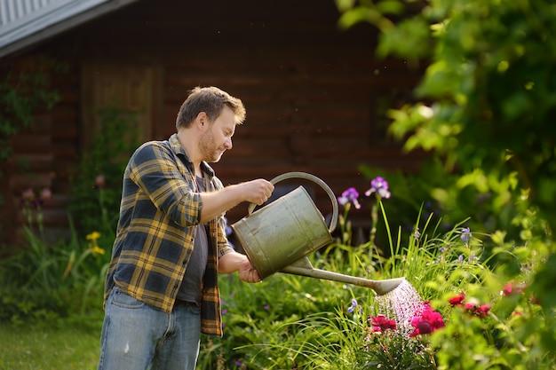 Flores molhando do homem considerável da idade média na jarda no verão.