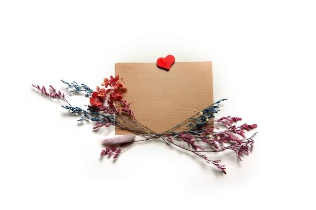 Flores multicoloridas secas e cartão para texto em um fundo branco.