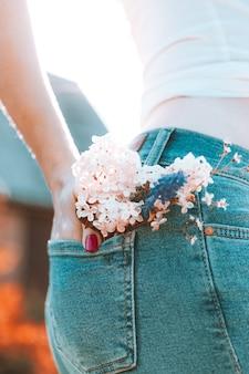 Flores no bolso de trás da calça jeans azul, uma menina com manicure vermelho