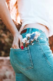 Flores no bolso de trás das calças de ganga, uma menina bonita em jeans