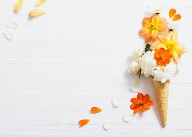 Flores no cone de waffle em fundo branco de madeira