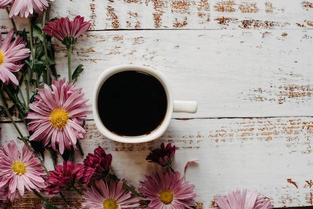 Flores no jardim, crisântemos e xícara de café sobre fundo branco de madeira