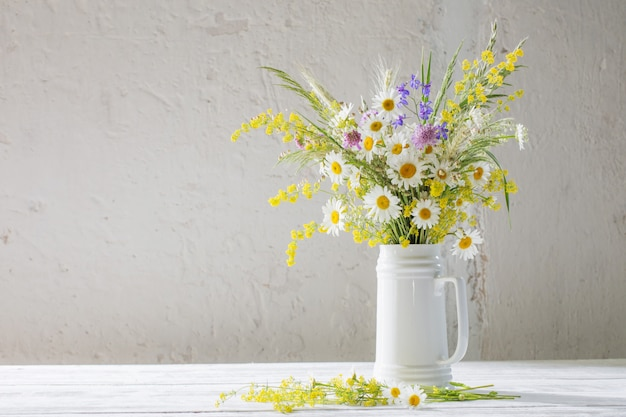 Flores no jarro branco sobre fundo branco