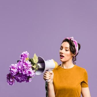Flores no megafone e mulher falando