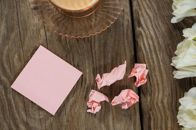 Flores, notas desintegradas e café na mesa de madeira
