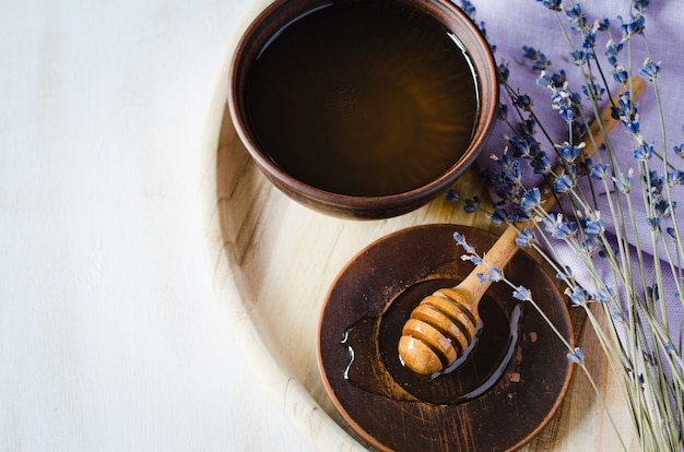 Flores orgânicas do mel e da alfazema na tabela de madeira.