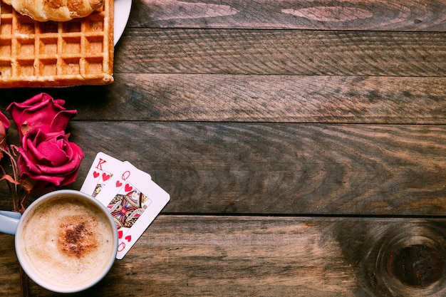 Flores, padaria no prato, cartas de baralho e copo de bebida