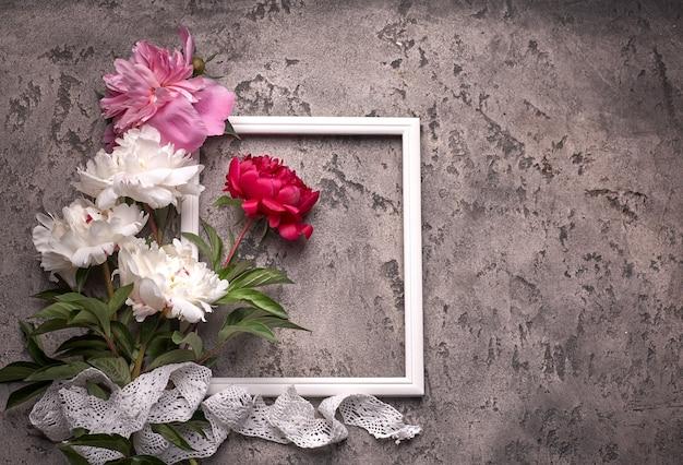 Flores paionies isoladas e quadro branco em fundo cinza.