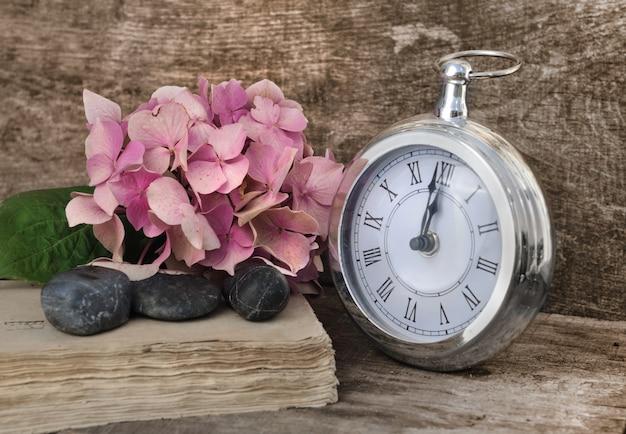 Flores, pedras e um relógio de bolso