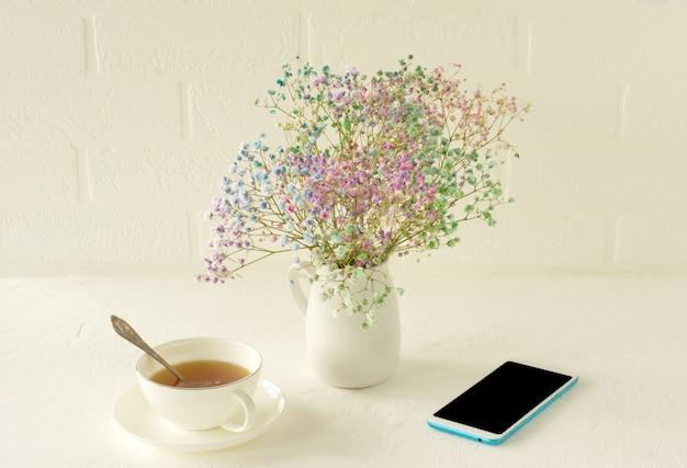 Flores pequenas de gypsophila coloridas em um fundo branco. decoração suave para a casa. flores. flores desabrochando em um vaso. sobre uma mesa com uma xícara de chá e smartphone.
