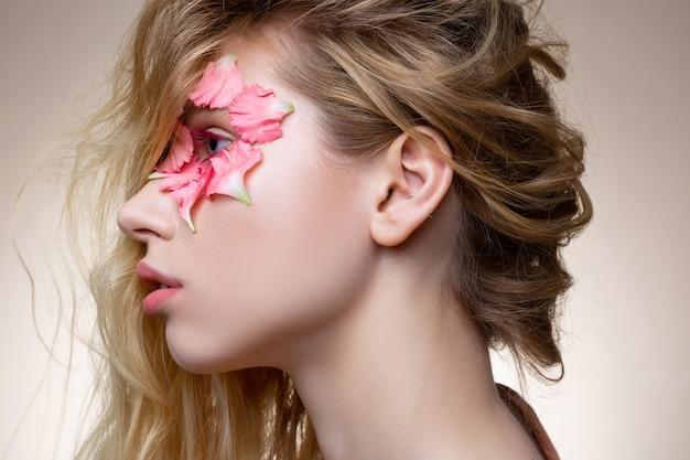 Flores perto do olho. modelo de cabelos loiros macios e atraentes com rímel rosa e flores perto dos olhos