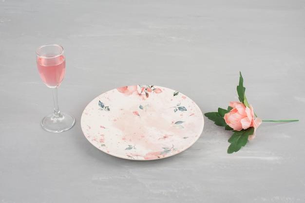 Flores, prato e uma taça de vinho rosé na superfície cinza.