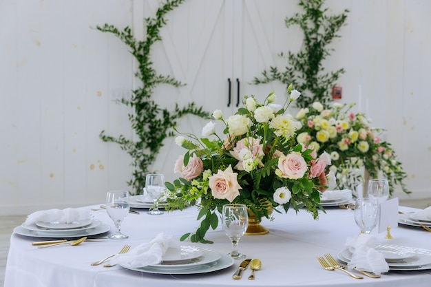 Flores, pratos brancos e copos servidos no jantar no restaurante.