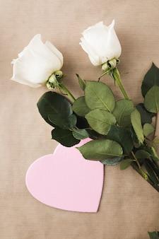 Flores rosas com coração de papel na mesa bege