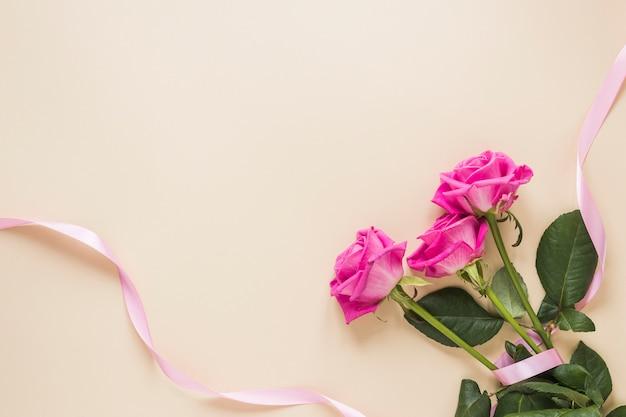 Flores rosas com fita na mesa