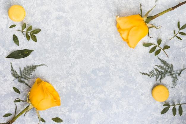 Flores rosas com macaroons e ramos de plantas
