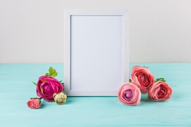Flores rosas com moldura em branco na mesa