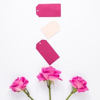Flores rosas com pequenos papéis na mesa