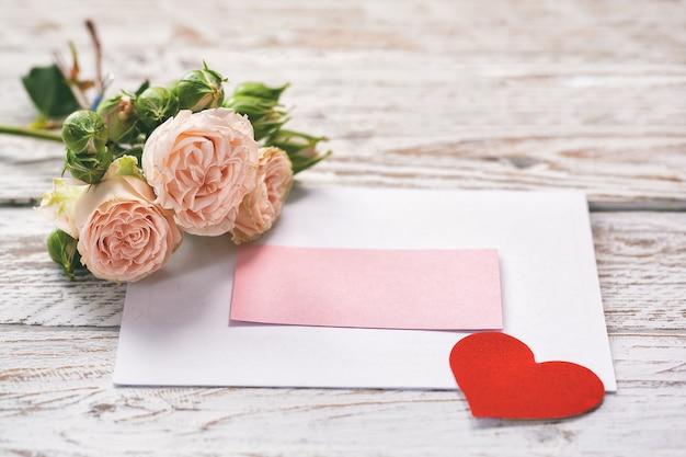 Flores rosas cor de rosa com cartão de presente e coração de papel vermelho em rosa
