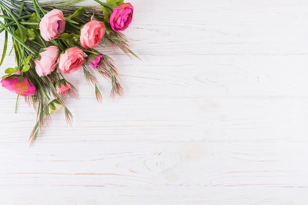 Flores rosas cor de rosa com ramos de plantas na mesa de madeira