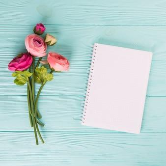 Flores rosas cor de rosa com um caderno em branco na mesa de madeira