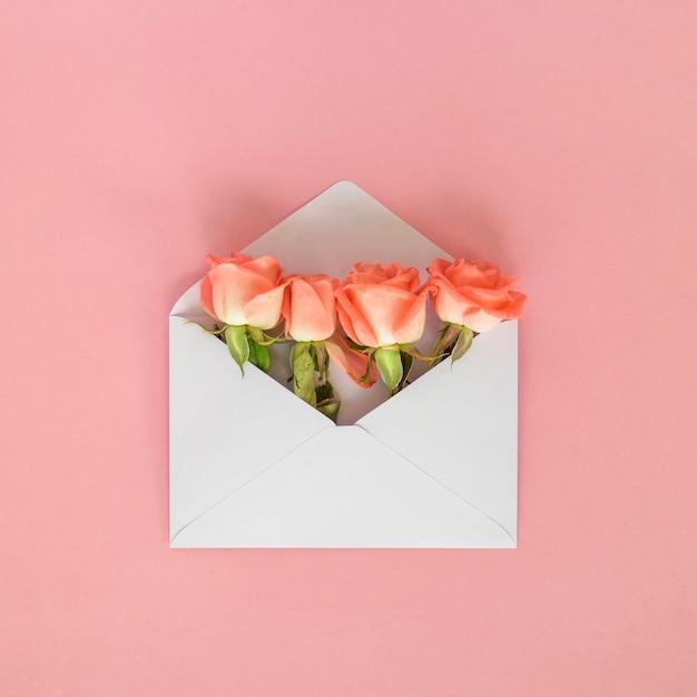 Flores rosas em envelope na mesa