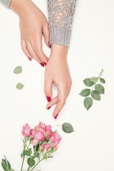 Flores rosas nas mãos da menina, vista de cima, vista de cima, pequenas rosas cor de rosa em branco