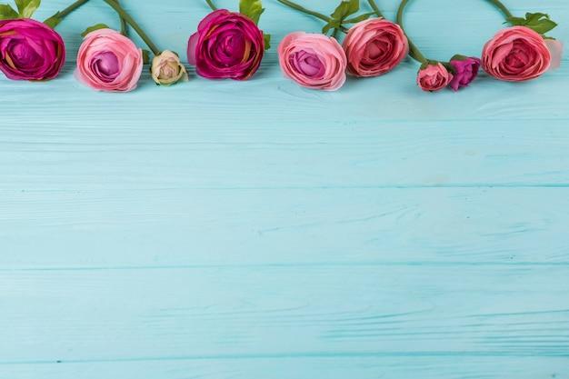 Flores rosas rosa espalhadas na mesa de madeira