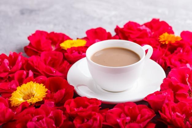 Flores rosas vermelhas e uma xícara de café em concreto cinza