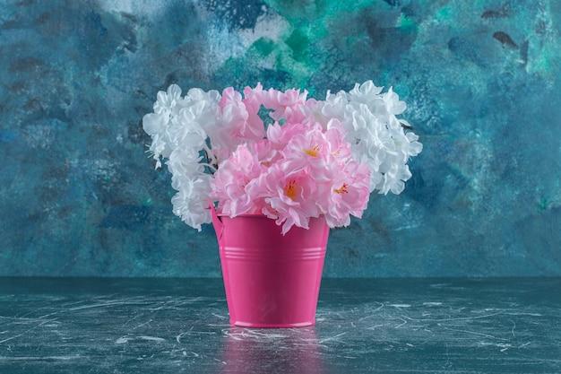 Flores roxas e brancas em um balde rosa, sobre fundo branco.