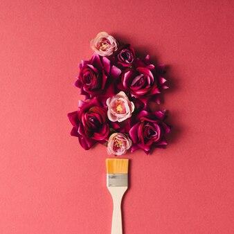 Flores roxas e pincel na parede rosa. postura plana.