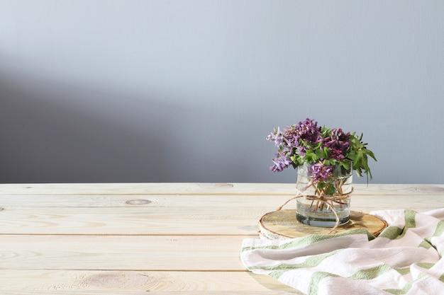 Flores roxas e toalha branca na mesa de madeira