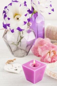 Flores roxas eustoma e vela acesa na mesa branca