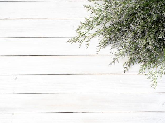 Flores roxas limonium em fundo branco de madeira