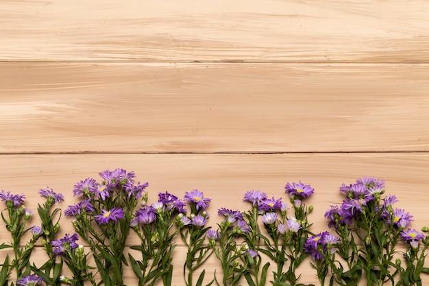 Flores roxas naturais em fundo de madeira