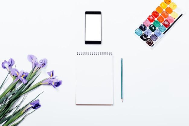 Flores roxas, telefone celular, caderno, lápis e tintas aquarela na mesa branca