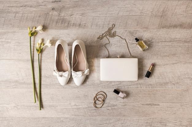 Flores; sapatos de vestido; embreagem; perfume; batom; verniz de unhas e hairbands em pano de fundo de madeira