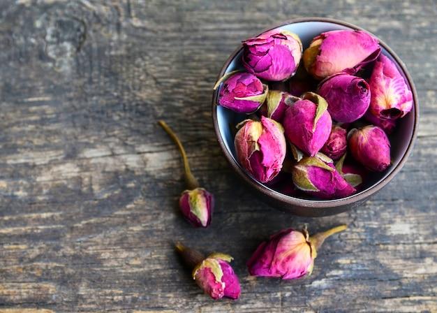 Flores secas de botões de rosa em uma tigela na mesa de madeira velha