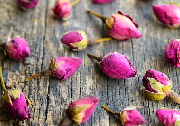 Flores secas de botões de rosa na mesa de madeira velha