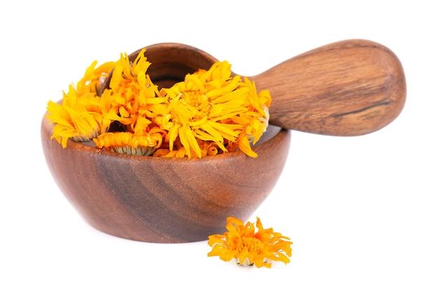 Flores secas de calêndula em uma tigela de madeira e colher isoladas em pétalas de calêndula de fundo branco