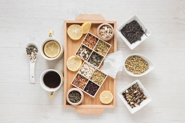 Flores secas de crisântemo chinês; ervas; fatias de chá e limão na bandeja de madeira