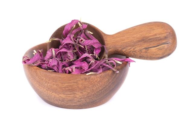 Flores secas de echinacea em uma tigela de madeira e uma colher, isoladas no fundo branco. pétalas de echinacea purpurea. ervas medicinais.